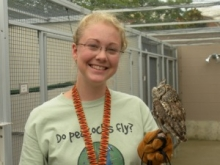 Student with mini owl perched on her hand