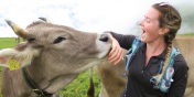 image description: a young woman smiling and leaning with an arm towards a brown horned cow