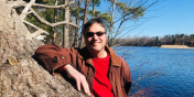 image description: a man in a brown jacket and red shirt is leaning against a rock near a body of water on a sunny day