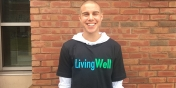 a white male is standing outside against a brick wall, smiling and is wearing a living well tshirt