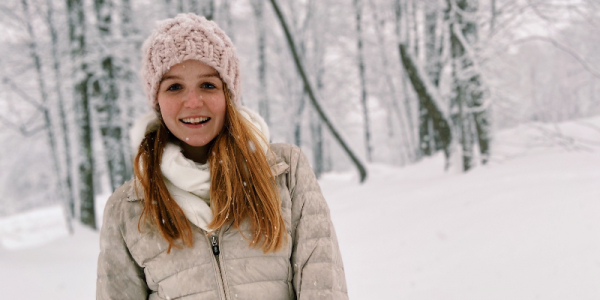 Emily Dow wearing a knit hat and winter coat, with a background of snow and trees