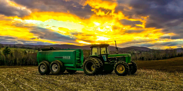 A tractor in a field with a sunrise behind