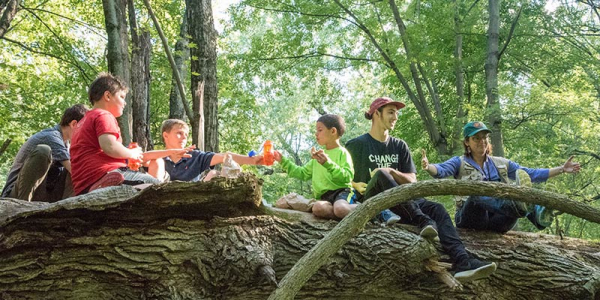 Several youths and their instructors in a forest sitting on a big log.