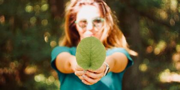 girl holding out large green leaf