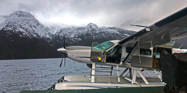 Sea plane docked beside snow-capped mountains in Alaska