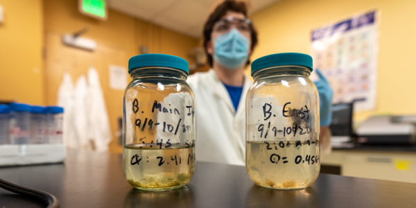 Ben Page displays two samples of wastewater in a science lab