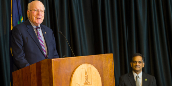 Senator Patrick Leahy speaks at a podium on stage with Suresh Garimella at the University of Vermont