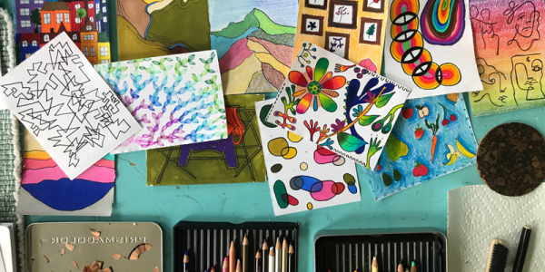 drawings and art supplies on a wooden table