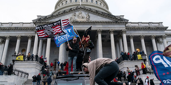 Protestors storm the U.S. Capitol Building, waving flags for Donald Trump