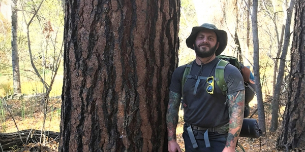 Jordan Luff stands next to ponderosa pine