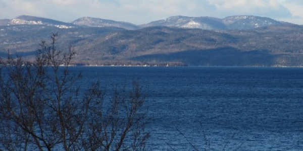 Snow covered mountains behind Lake Champlain