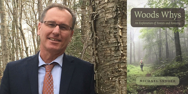 Michael Snyder leans against a yellow birch in the woods and his new book