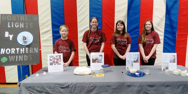 4-H participants stand with candle exhibit