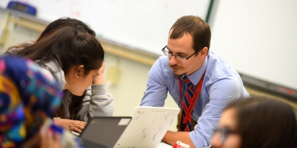 Tom Payeur instructs a student while using a laptop