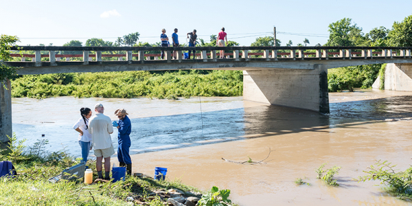 Researchers stand on bank of river in Cuba with onlookers on bridge