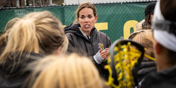 Women's lacrosse coach Sarah Dalton talks to University of Vermont student athletes