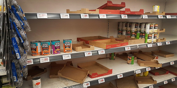 Empty grocery shelf with a few cans of beans