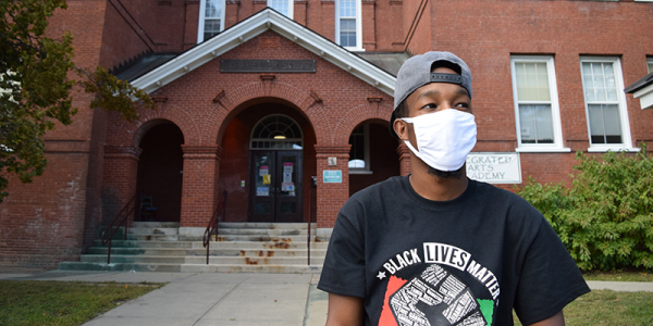 Aden Haji stands in front of Integrated Arts Academy in Burlington's Old North End.