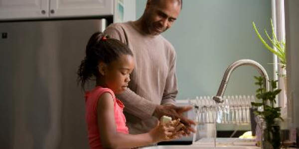 A father doing dishes with his daughter