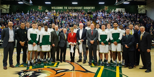 Men's basketball players and university leaders join Rich and Deb Tarrant on the basketball court with fans in bleachers behind them