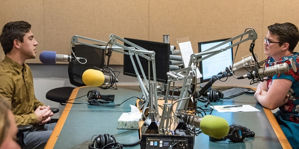 A science student sits opposite Vermont Public Radio host Jane Lindholm, talking into microphones in a studio.