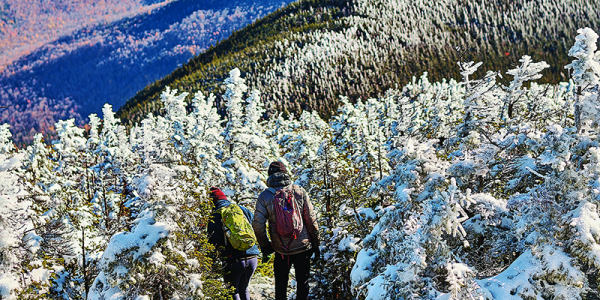 Two hikers with backpacks along the snowy ridgeline on Mount Abraham