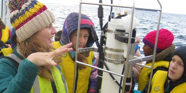 College student shows three middle school students equipment on a research vessel