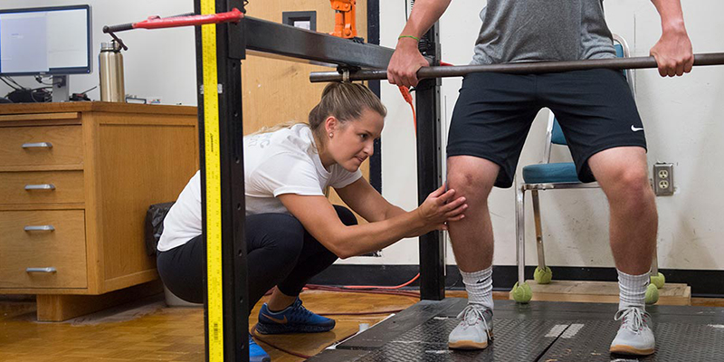 Kristina Ushakova examines knee of athlete