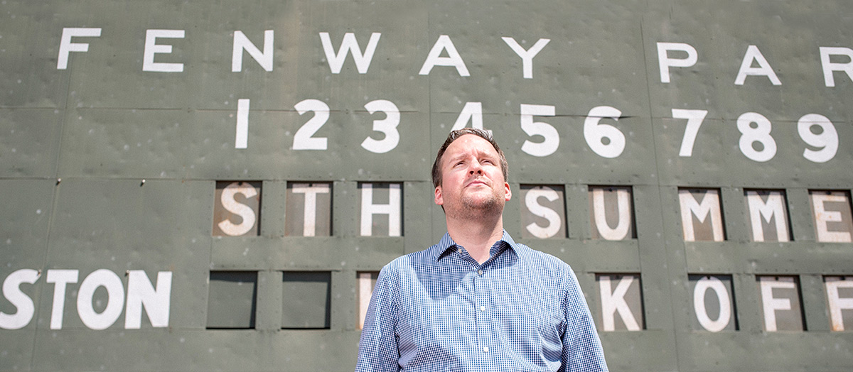 A man stands in front of the scoreboard at Fenway Park